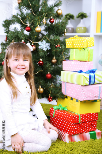 Little girl with presents near Christmas tree in room