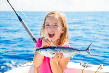 Blond kid girl fishing tuna little tunny happy with catch