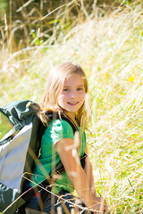 Blond explorer kid girl walking with backpack in grass