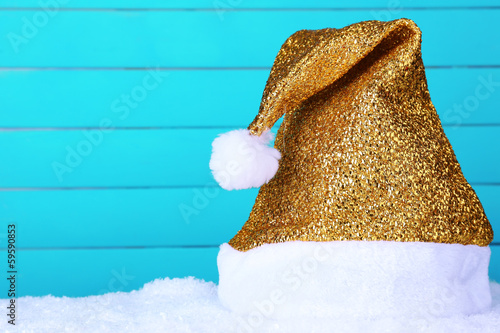 Santa hat on snow on color wooden background