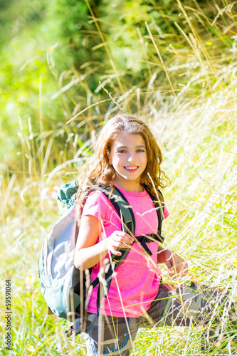 Explorer kid girl walking with backpack in grass