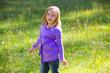 Blond kid girl happy in outdoor green meadow