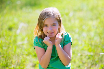 Blond kid girl excited gesture expression in green outdoor