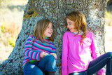 Sister kid girls smiling sit relaxed in a oak tree trunk