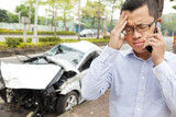 upset driver talking on mobile phone with wrecked car