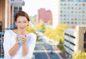 Beautiful woman drinking coffee on balcony of her apartment