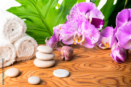 Spa and wellness setting with orchid, pebbles and towel