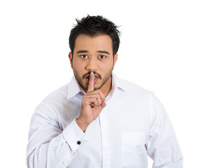 Man placing finger on lips as if to say, shh, be quiet
