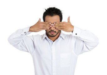 Man covering eyes with hands can't see. See no evil concept.