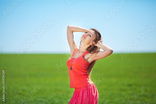 Portrait of a woman in red on a background of sky and grass