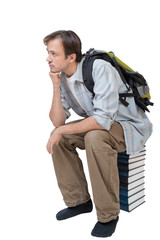 Young with backpack sits on stack of books