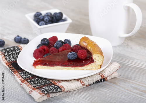 Slice of raspberry pie with fresh berries on a plate