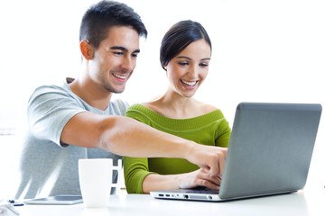 Happy young couple browsing internet at home