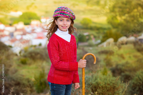 Kid girl shepherdess with wooden baston in Spain village