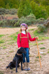 Kid girl shepherdess happy with dog and flock of sheep