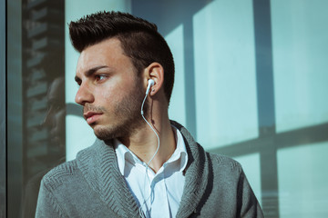 Portrait of a handsome young man listening to music