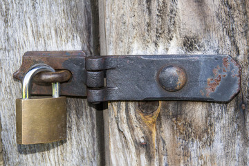 Close up of padlock and old metal hasp and staple