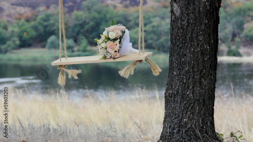 Wedding rose bouquet on the swing in front of the river