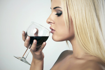 Beautiful Blond woman drinking red wine.wineglass. Beauty