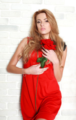 Passionate woman with red rose in studio, girl and flower