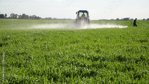 Tractor spray fertilize field with insecticide. farmer meter