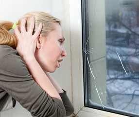 The sad young woman near a window with the burst, broken glass..