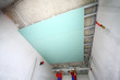 two workers install ceiling profile in new apartment