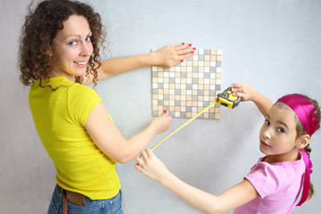 Daughter helps mother to measure the finishing tile