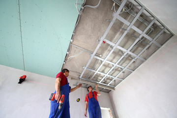two workers set the ceiling profile in the new flat