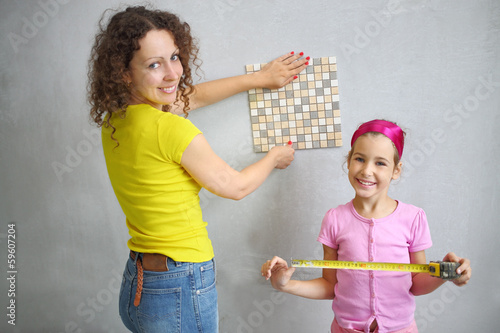 daughter helps her mother to measure the finishing tile