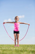 Little girl on nature of the jumps with a skipping rope