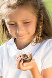 portrait of smiling little girl with large snail in hand
