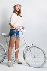 Young smiling woman with a white vintage bicycle