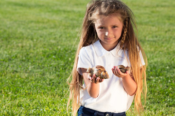 A few snails in hands of little girl with long hair