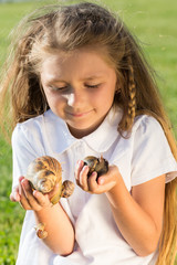 snails crawling on hands of little girl with flowing hair
