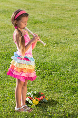 Little girl playing fife on green grass with flowers.