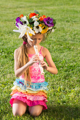 Girl with wreath of flowers on head playing pipe on grass.