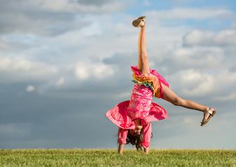 The little girl turns like wheel on grass