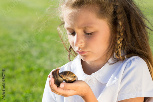 Close-up portrait of little girl with large snail in hand