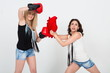 girls in denim shorts having fun, one with boxing gloves other