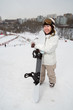 Smiling girl snowboarder stands on hill with snowboard