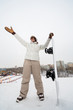 Girl snowboarder stands on hill with snowboard