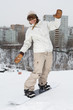 Smiling girl snowboarder sliding on snow on a hill