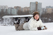 Smiling girl snowboarder lying in snow on hill with snowboard