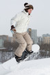 Girl snowboarder jumping on the snow on a hill