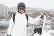 Smiling girl snowboarder in helmet stands on hill