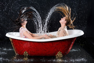Two wet girls with closed eyes create hair splashes water