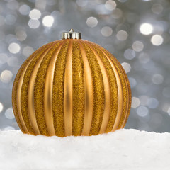 Big golden Christmas ball on snow over festive background