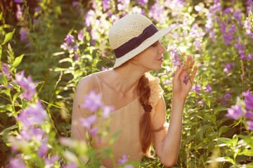 Beautiful woman enjoying the scent of wildflowers