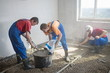 Three worker prepare the mixture and pouring floor